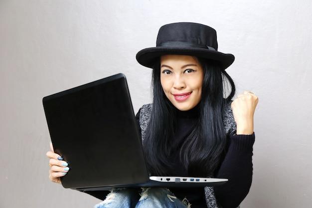 Empresaria, encantadora piel bronceada hermosa negocios asiáticos chic mujer mano trabajo en computadora portátil y éxito mano arriba