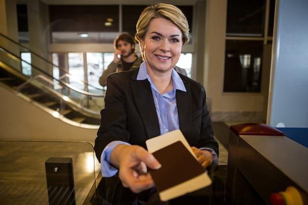 Empresaria entregando su tarjeta de embarque en el mostrador