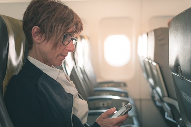 Empresaria enviando un mensaje con el teléfono móvil mientras está sentado en el avión antes de la salida.