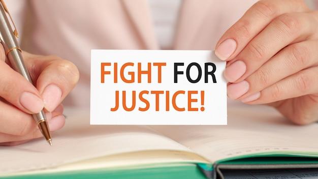 La empresaria escribe en un cuaderno con un bolígrafo plateado y una tarjeta de mano con texto: lucha por la justicia.