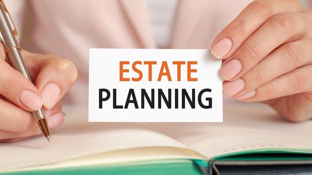 La empresaria escribe en un cuaderno con un bolígrafo plateado y una tarjeta de mano con texto: planificación inmobiliaria