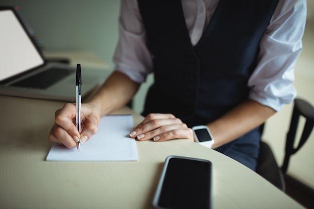 Empresaria escribiendo en el bloc de notas