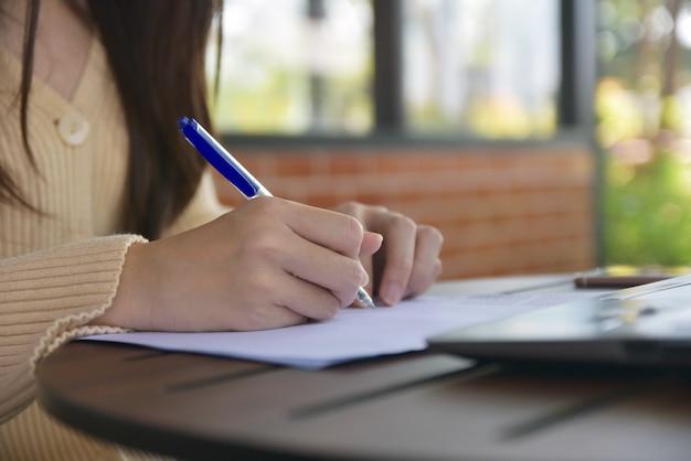 Empresaria escribiendo en el documento en la oficina