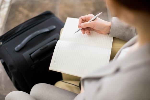 Empresaria escribiendo notas en viaje