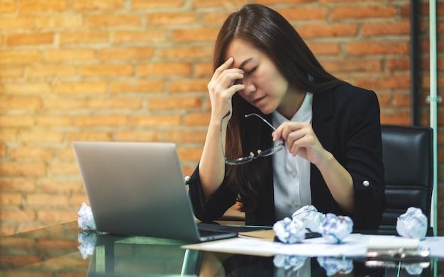 La empresaria se estresa con papeles y computadoras portátiles en la mesa mientras tiene un problema en el trabajo en la oficina