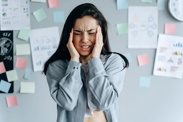 Empresaria estresada cansada que siente un fuerte dolor de cabeza masajeando las sienes agotadas por el exceso de trabajo