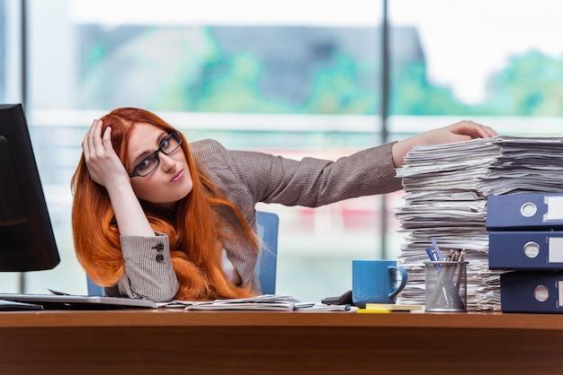 Empresaria estresada con pila de papeles