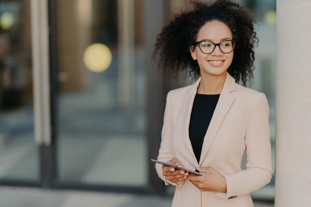 Empresaria exitosa positiva con cabello afro tiene tableta digital, se encuentra al aire libre cerca del edificio de oficinas