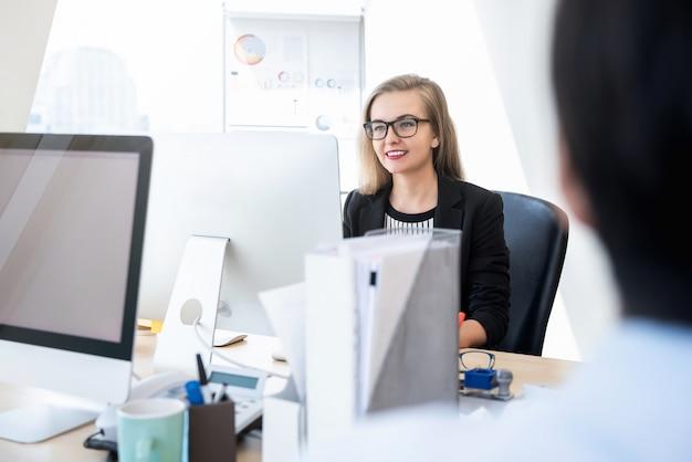 Empresaria feliz trabajando con la computadora en la oficina