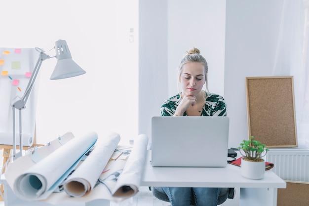 Empresaria femenina que trabaja en la computadora portátil en el lugar de trabajo