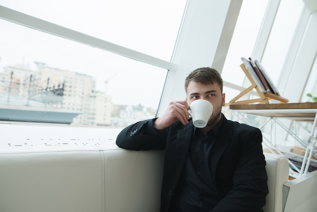 Una empresaria guapo sentado en un café en la ventana y tomando café. coffee break en la elegante cafetería moderna