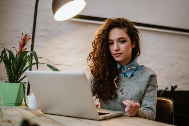 Empresaria hermosa joven concentrada que trabaja en el ordenador portátil en oficina moderna brillante.