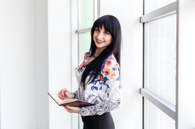 Empresaria hermosa joven que se coloca cerca de la ventana, escribiendo en un cuaderno, mirando la sonrisa de la cámara.