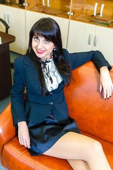 Empresaria hermosa joven que descansa mintiendo en un sofá en oficina