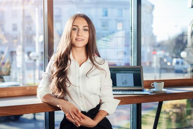 Empresaria hermosa joven que sonríe y que mira la cámara