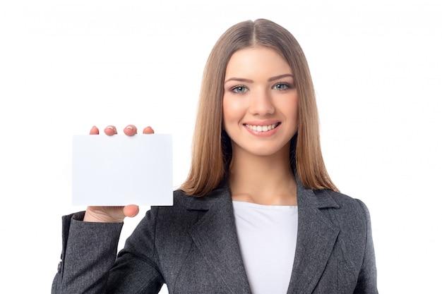 Empresaria hermosa joven que sostiene el trozo de papel en blanco para el espacio de la copia