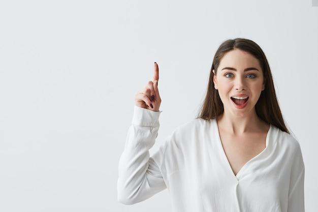 Empresaria hermosa joven sorprendida con la boca abierta que sonríe señalando el dedo para arriba.