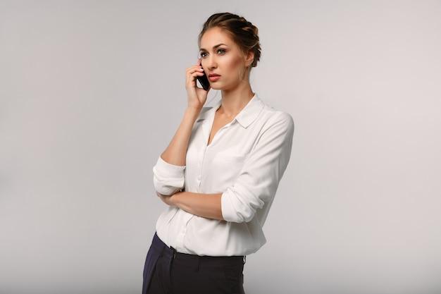 Empresaria hermosa con un teléfono celular en manos. conversación seria retrato de negocios