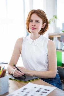 Empresaria hipster pensativa sentada en su escritorio con una tableta de dibujo digital