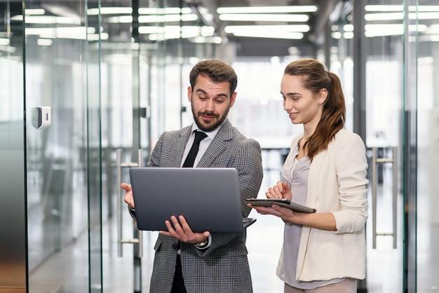 Empresaria y hombre de negocios en la computadora portátil que se coloca y que discute proyecto en ventanas vacías de la oficina con vista a la ciudad.