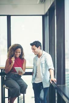 Empresaria y hombre de negocios que miran la tableta juntos