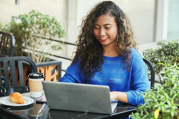 Empresaria indonesia sonriente que hojea la computadora portátil en café