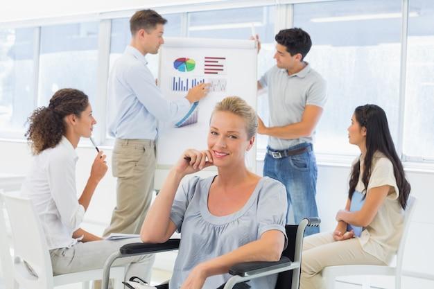Empresaria informal en silla de ruedas sonriendo a la cámara durante la presentación