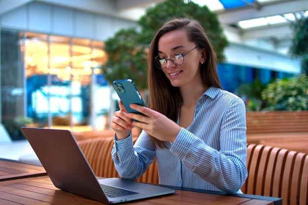 Empresaria inteligente casual moderna que usa el teléfono y la computadora portátil para trabajar de forma remota en línea en un lugar público