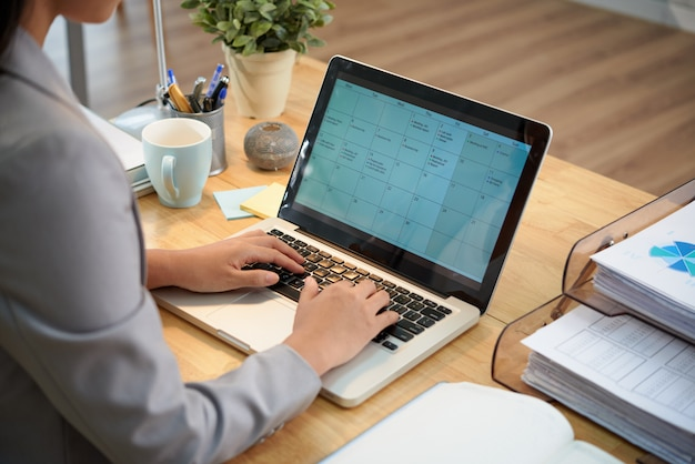 Empresaria irreconocible sentado en el escritorio con la computadora portátil y mirando el calendario