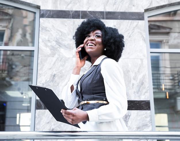 Una empresaria joven africana que habla en el smartphone que sostiene el tablero disponible