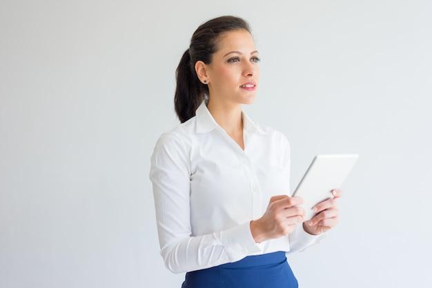 Empresaria joven ambiciosa pensativa que usa el dispositivo moderno.
