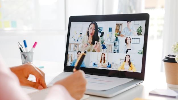 La empresaria joven de asia que usa la computadora portátil habla con el colega sobre el plan en la reunión de la videollamada mientras trabaja desde casa en la sala de estar.