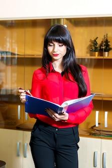 Empresaria joven en blusa roja con una carpeta de documentos en oficina