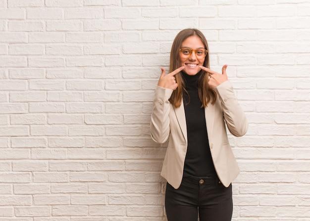 La empresaria joven bonita del empresario sonríe, señalando la boca