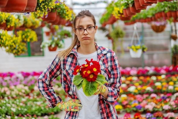 Empresaria joven cansada de pie en invernadero y sosteniendo una olla con flores