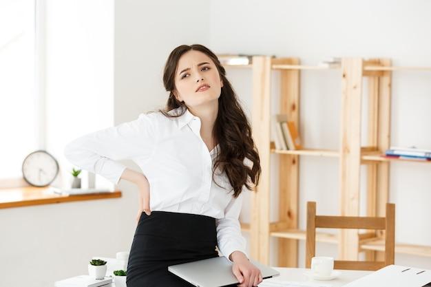 Empresaria joven cansada que sufre de mucho tiempo sentado en el escritorio de la computadora en la oficina.