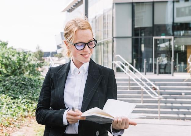Empresaria joven confiada que se coloca fuera de la oficina que mira el diario