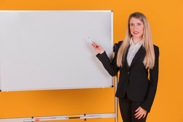 Empresaria joven confiada que da la presentación contra un contexto anaranjado