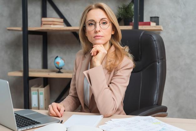 Empresaria joven confiada que se sienta en el lugar de trabajo con el ordenador portátil en la oficina