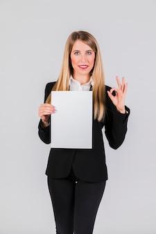 Empresaria joven confiada que sostiene el libro blanco que muestra la muestra aceptable en fondo gris