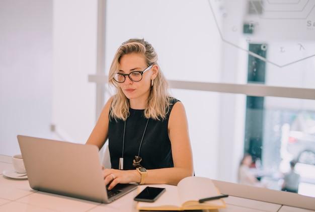 Empresaria joven confiada que usa el ordenador portátil en el lugar de trabajo en la oficina