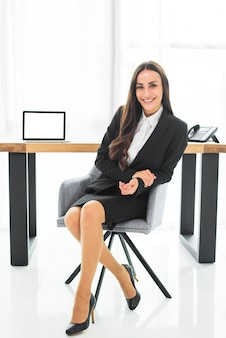 Empresaria joven confiada sonriente que se sienta en silla