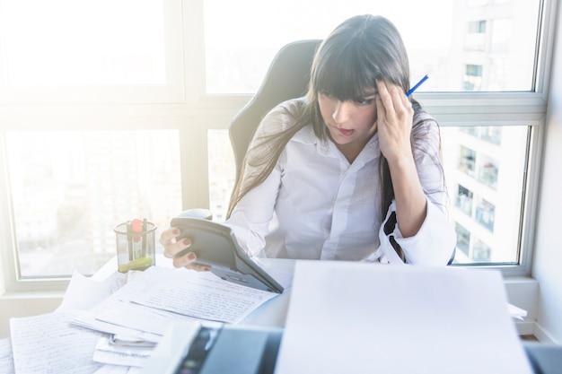 Empresaria joven contemplada que mira la calculadora en el lugar de trabajo