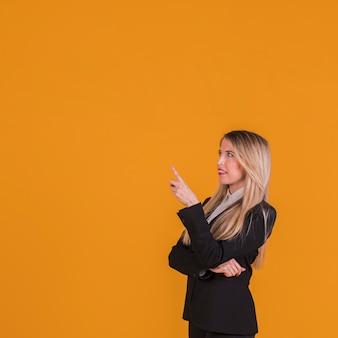 Empresaria joven contemplada que señala su dedo contra un fondo anaranjado