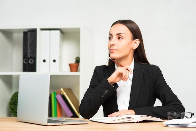 Empresaria joven contemplada que se sienta en el escritorio de oficina con el ordenador portátil en el escritorio
