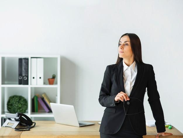 Empresaria joven contemplada que sostiene las lentes disponibles que se colocan detrás del escritorio de oficina