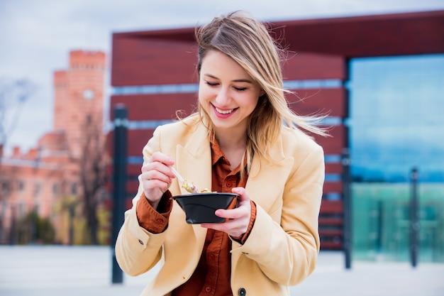 Empresaria joven con la ensalada en la ciudad urbana al aire libre.