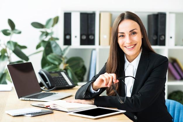 Empresaria joven feliz confiada que se sienta en el escritorio de oficina