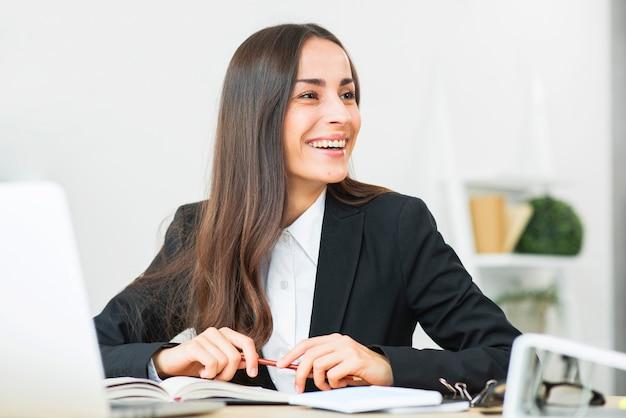 Empresaria joven feliz que se sienta en el escritorio de oficina que mira lejos