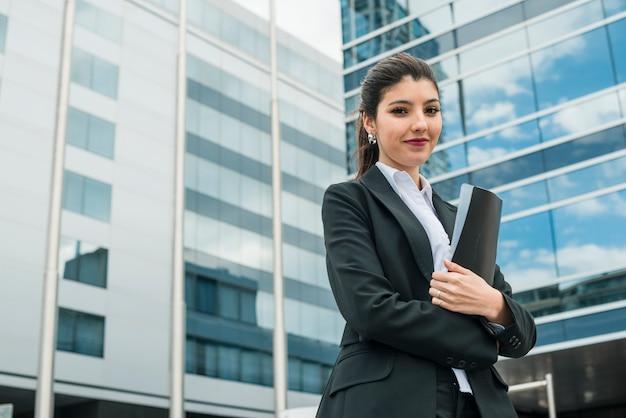 Empresaria joven feliz que sostiene la carpeta en la mano que se coloca delante del edificio
